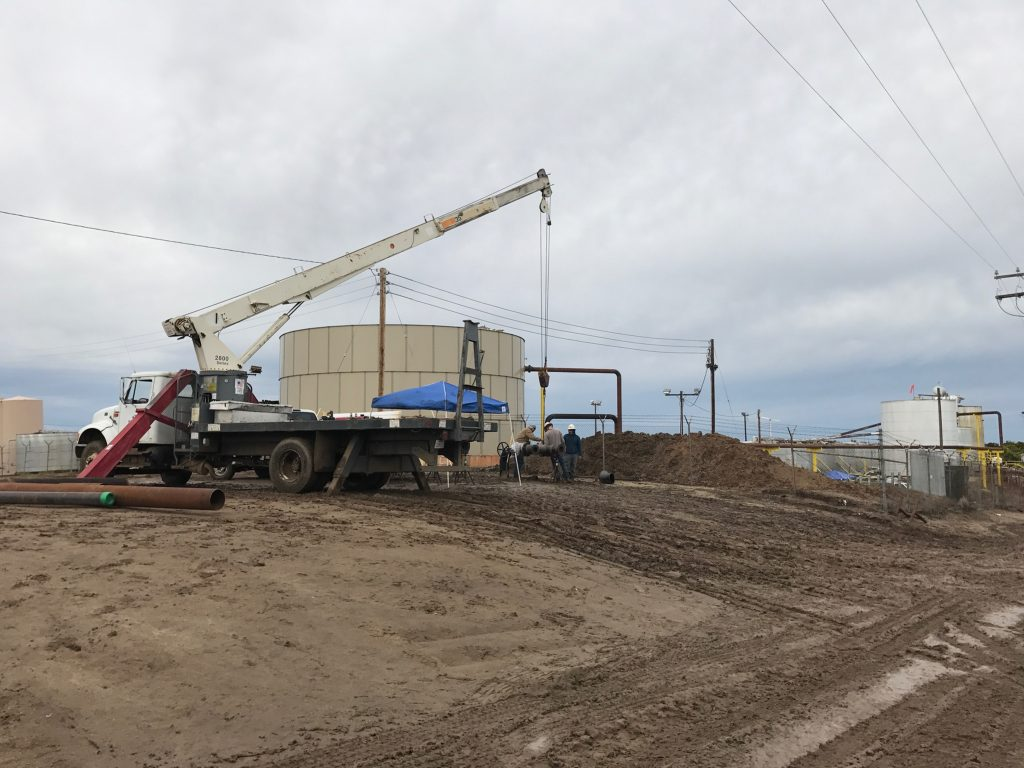 truck crane lowering pipe into ground to connect to water tank with asset management team